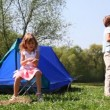 Little boy and girl plays near blue tent at forest in summer day — Stock Video