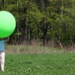 Boy holds over his head large inflatable green ball, then throws of its up high and goes behind it at forest on summer day — Stock Video #27974737
