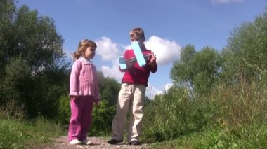 Little girl and boy stand in park, boy launch toy plane. Sunny summer day. — Stock Video
