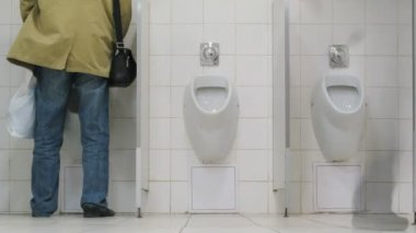 Men using urinals in supermarket toilet — Vídeo de stock