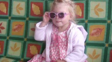 Petite fille à lunettes de soleil et une robe rose secoue sur une balançoire. — Vidéo