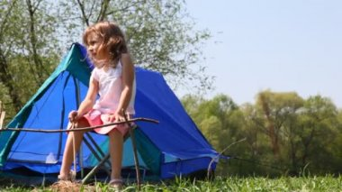 Nice little girl sits on chair with wooden stick in his hand near small blue tent at forest summer day — Stock Video