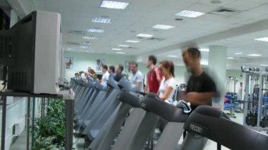 People watch TV on treadmills at Multisport fitness club — Stock Video