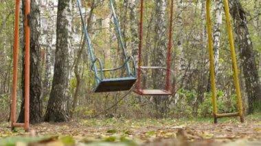 Two swings swaying in park — Stock Video