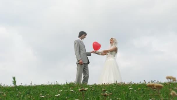 Couple de jeunes mariés pose avec ballon coeur devant ciel nuageux — Vidéo