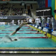Sportsmen in relay, some finish backstroke, others start breaststroke — Stock Video
