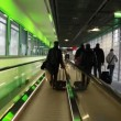 Stock Video: People go to corridor horizontally moving escalator at exit