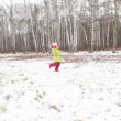 Stock Video: Little girl in green jacket is turned in winter wood.