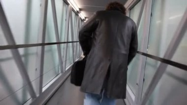 Hombre camina a lo largo de un pasillo estrecho con paredes de cristal — Vídeo de stock