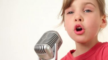 Bella ragazza canta nel microfono su sfondo bianco — Video Stock