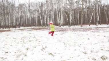 Little girl in green jacket is turned in winter wood. — Stock Video