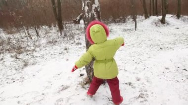 Cute little girl dances round a tree in winter wood. — Stock Video