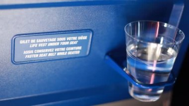 Glass of water standing on support to back chair airplane — Stock Video