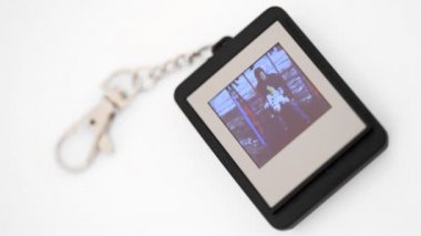 Electronic trinket with liquid-crystal display showing family photos — Stock Video