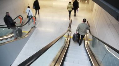 People run down steps of moving escalator — Stockvideo