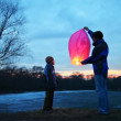 Man holds chinese lantern of winter forest, its son looks and touches it — Stock Video