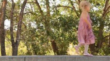 Smiling little girl in an elegant pink dress on stone border — Stock Video