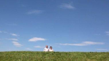Ouder paar praten komt op heuvel, stop en met overdekte hand van zon ziet er weg — Stockvideo