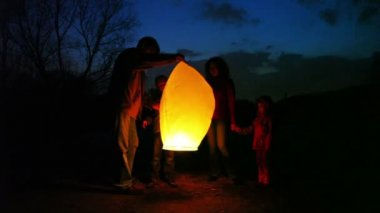 Man lifts glowing chinese lantern, its wife joking forces hands air, son and daughter look — Stock Video