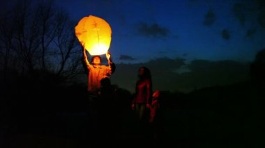 Man does some attempts to start glowing chinese lantern, its wife with son and daughter look — Stockvideo
