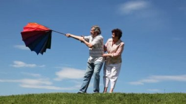 Mature couple stands and pulls strongly curved umbrella by wind — Stock Video