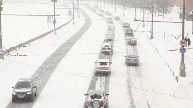 город дорожного движения проходит alonf реки под снегопад — Стоковое видео