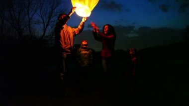 Man holds glowing chinese lantern at night, its wife joking forces hands air, son and daughter look — Stock Video