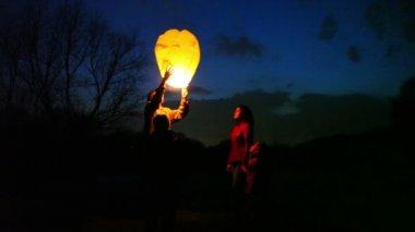 Man does attempt to start glowing chinese lantern, then gives its wife, son and daughter look — Stock Video