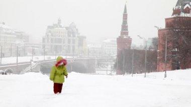 Girl plays with snow near Moscow Kremlin under snowfall — Stock Video