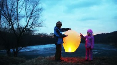Boy and girl holding, gently touch chinese lantern in winter woods — Stock Video