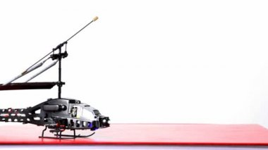 Toy helicopter is on table, its blades start to rotate, then flies up upwards — Stock Video