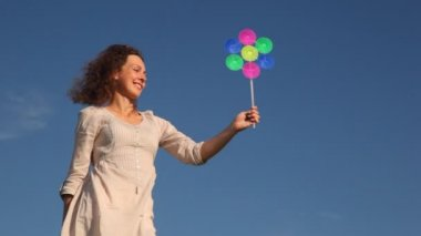 Closeup cute young woman holds in her hand colorful toy windmill spinning at wind against sky — Stock Video
