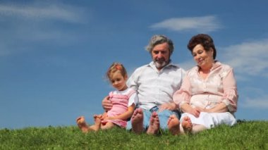 Mature couple and granddaughter sat wiggling their bare feet on grass — Stock Video