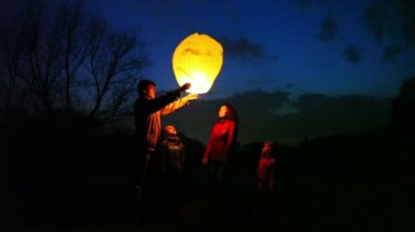 Man takes glowing chinese lantern from wife, does attempts to start it, she with son and daughter look, part1 — Stock Video