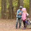Little girl and boy stand with bicycle in park. — Stock Video