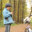 Boy with mobile phone stands near to bicycle in park. — Stock Video #28063957