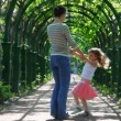 Mother and little daughter rotate holding hands in arched corridor braided plants — Stock Video