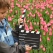Boy says, claps clapperboard on many pink tulips field — Vídeo de stock