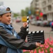 Boy claps clapperboard and goes out of frame at bed with tulips on city streets — Vídeo de stock