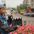 Boy with cinema clapper board is on city streets — Vídeo de stock