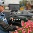 Boy with cinema clapper board hands stands on streets — Vídeo de stock