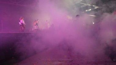 Bailarines aparecen en el escenario iluminado de humo — Vídeo de stock