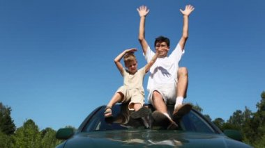 Father and son sitting on roof of car, then they waved with both hands — Stock Video