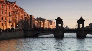 Huis en bridge lomonosov aan gracht verlicht door de zon instelling in centrum st.petersburg — Stockvideo