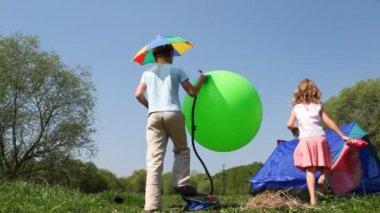 Boy pumps rubber ball, little girl goes inside tent — Stock Video
