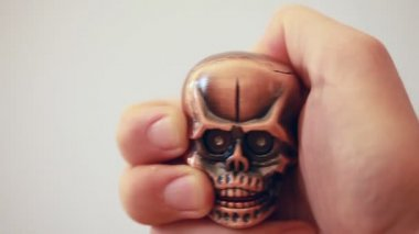 Revolving lighter in shape of tiny cranium with glow eyes in hand — Stock Video