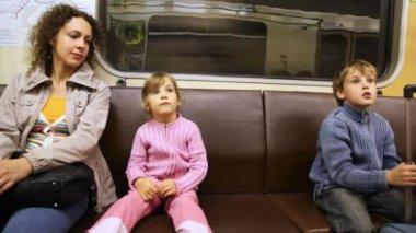 Mãe com filha e filho sentar no andar de trem de metrô — Vídeo Stock