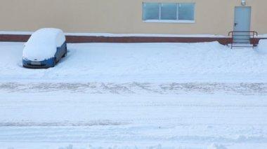 трактор чистит снег на дороге, движется вниз по улице в зимний период — Стоковое видео