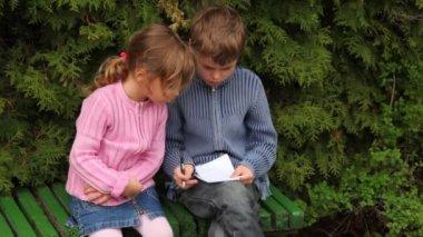 мальчик и девочка сидеть на скамейке возле деревьев — Стоковое видео