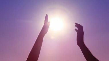Hands of man and woman contacting against sun on sky — Stock Video